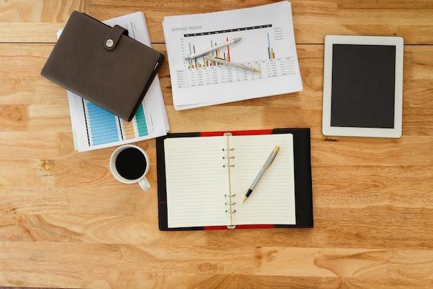 Деревянный офисный стол с канцелярскими принадлежностями и кофейной чашкой. вид сверху