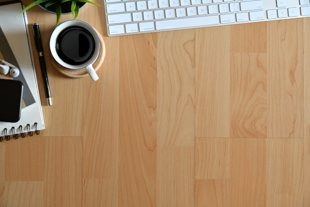 Wooden office desktop with keyboard computer, coffee mug ,office supplies and copy space