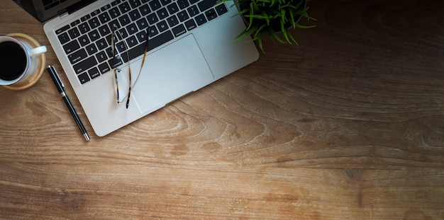 Wooden office table with laptop and copy space