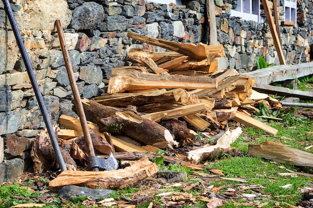 A wooden, old ax near stone wall against the background of chopped firewood. nepal