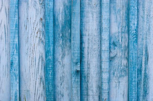 Деревянный старый синий забор с шелушением и потрескавшейся краской