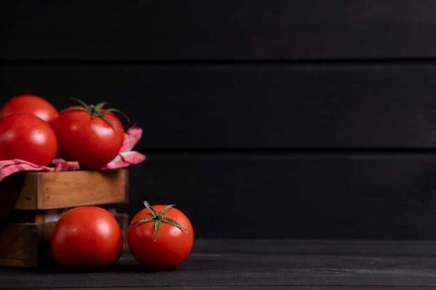 A wooden old box full of fresh red juicy tomatoes . high quality photo
