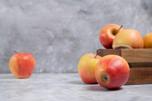 Una vecchia scatola di legno piena di frutti maturi freschi di mela rossa posizionati su uno sfondo di marmo. foto di alta qualità