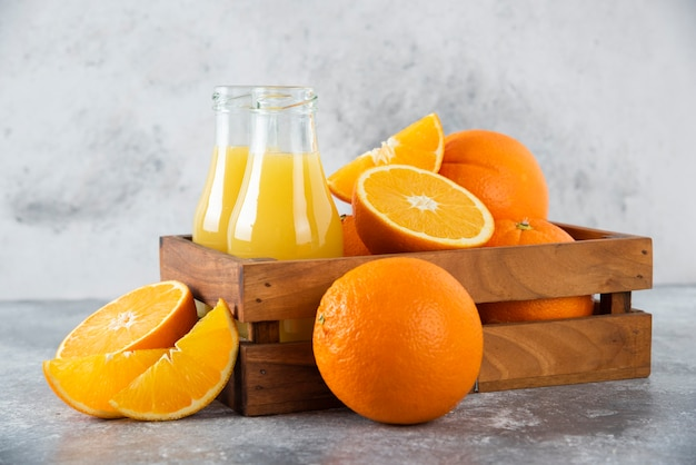 A wooden old box full of orange fruits and glass pitchers of juice on stone table .