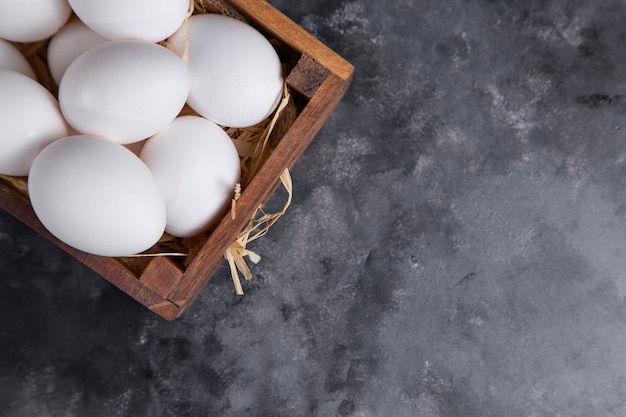 A wooden old box full of raw white chicken eggs .