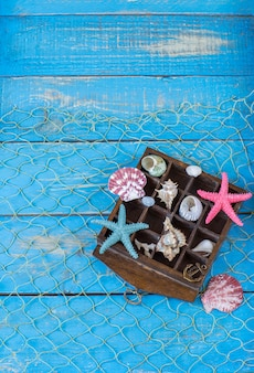 In a wooden old box: shells, starfishes, marine decor.