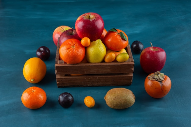 Wooden old box with various types of fresh juicy fruits placed on marble table .