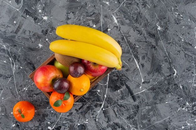 大理石のテーブルに置かれた新鮮なジューシーな果物の様々な種類の木製の古い箱。