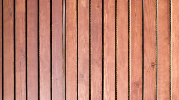 Wooden old brown vertical railing on the whole background.