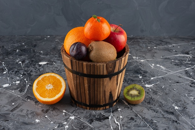 Wooden old bucket with various types of fresh juicy fruits placed on marble table .