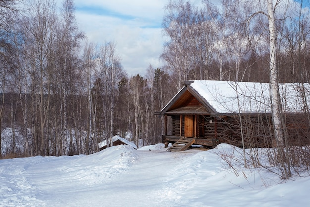 Wooden old house in the forest in snowy winter