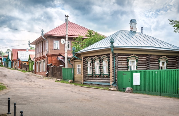 Wooden old houses on nikolskaya street in plyos under a cloudy summer sky. caption: house with dragons