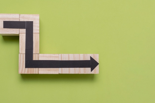 Wooden outline of an arrow on green background