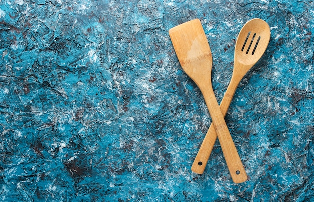Wooden paddles for cooking on a blue concrete table. top view