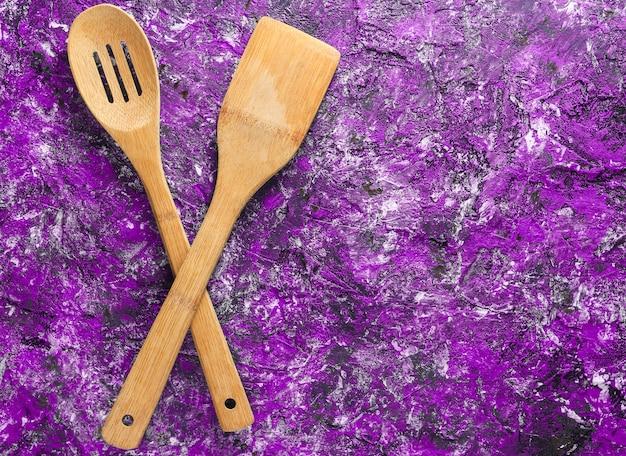 紫色のコンクリートの背景で調理するための木製のパドル
