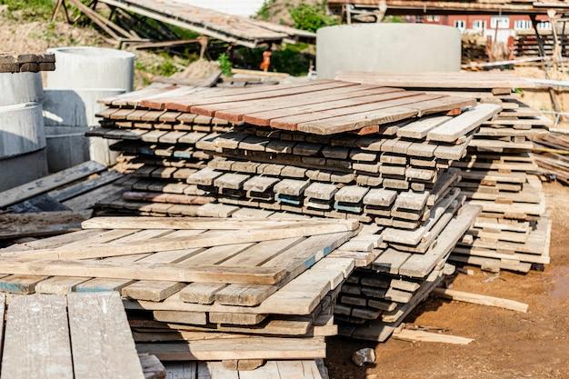 Деревянные поддоны на строительной площадке. повторное использование строительных материалов. инструмент для мощения.