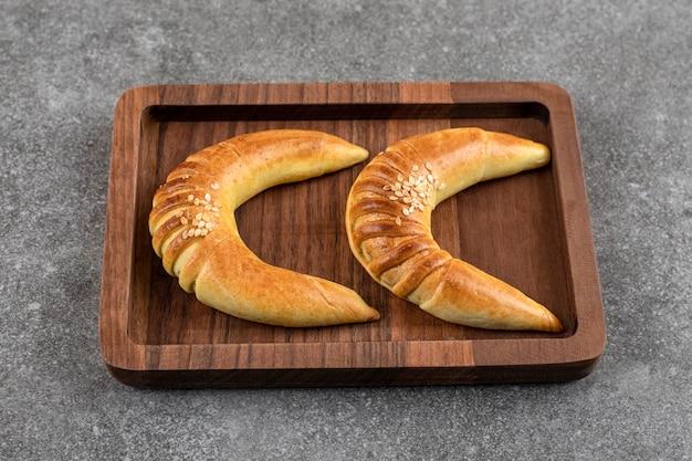 大理石のテーブルに2つのおいしい三日月形のバニラクッキーの木製パテ。