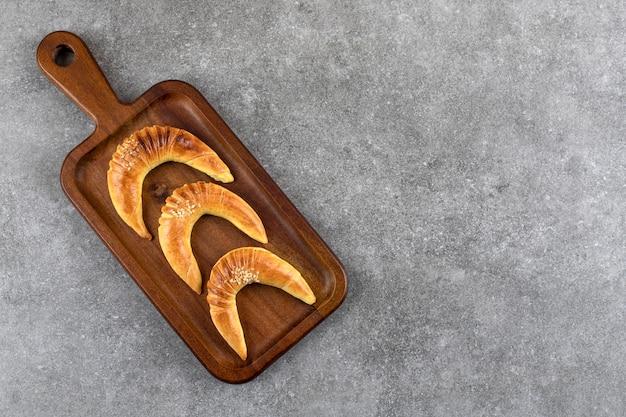 Patè di legno di tre deliziosi biscotti alla vaniglia a forma di mezzaluna su marmo.