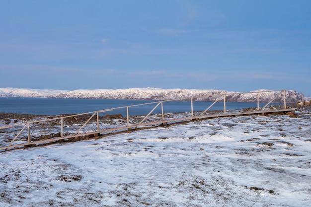 雪に覆われた冬のツンドラを通る山の上の木製の小道。