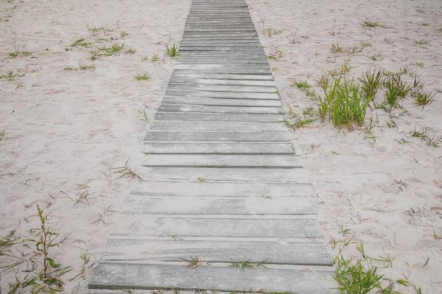 Деревянная дорожка на песчаном пляже в окружении следов