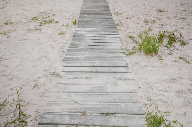 Wooden pathway on the sand beach surrounded with footprints
