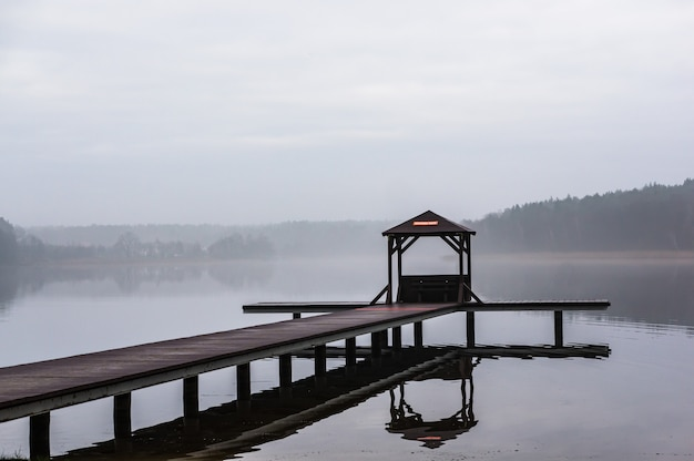 Wooden pathway above the water surrounded by trees with a foggy background