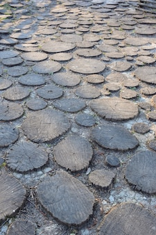 Wooden pavement made of many round sawn wood stumps dug into the ground of various shapes