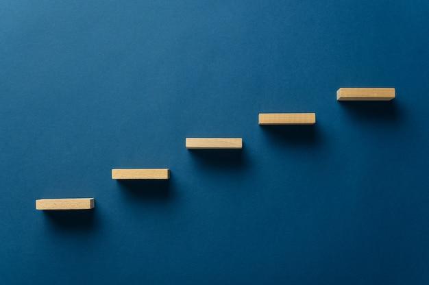 Деревянные колышки размещаются на темно-синем фоне в конструкции, подобной лестнице на концептуальном изображении. с копией пространства.