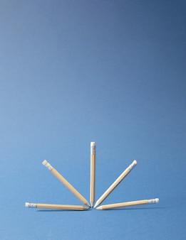 木製の鉛筆、ハーフボールに配置された浮揚。最小限のクリエイティブオフィス/学校/ビジネスコンセプト。青い背景。