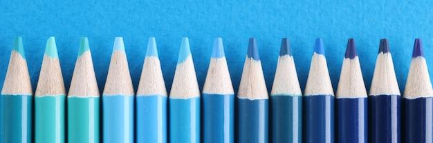 水色の背景にさまざまな青い色合いの木製の鉛筆