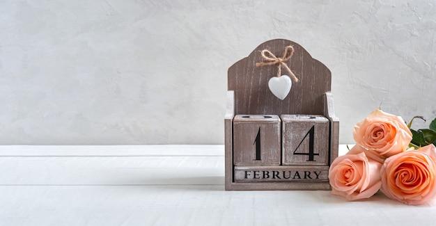 2月14日の日付の木製の永久カレンダーとバラの花束。バレンタインデーのシンボル。はがき。より良いプロジェクトのための空き容量。