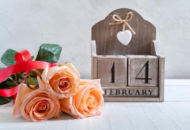 2月14日の日付の木製の永久カレンダーとバラの花束。バレンタインデーのシンボル。はがき。