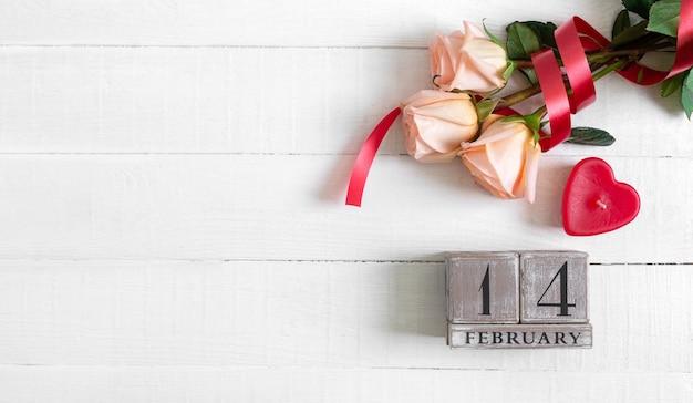 2月14日付けの木製の永久カレンダー、キャンドルハートとバラの花束。コンセプトバレンタインデー。
