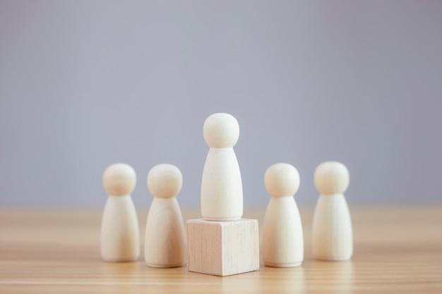 黒の背景の人々の間で木製の人モデルリーダーシップの概念