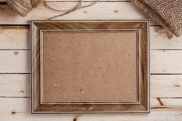 Wooden photo frame on light wooden background, top view, copysàce