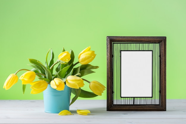 A wooden photo frame near yellow tulips on a wooden surface