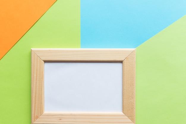 カラフルな紙の背景に木製のフォトフレーム。