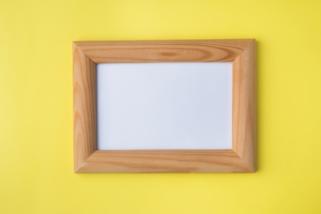 Wooden photo frame on yellow