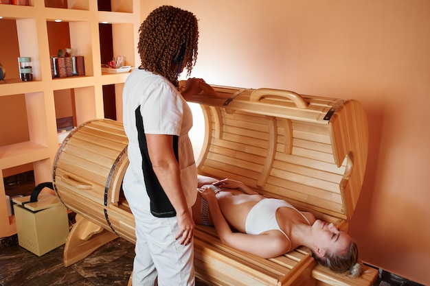 Wooden phyto barrel, horizontal sauna. beautiful woman massage therapist applying spa treatment to a young woman in a wellness room