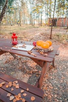 秋の森の木製ピクニックテーブル。自然の中でリモートワークの概念。秋の季節の時間