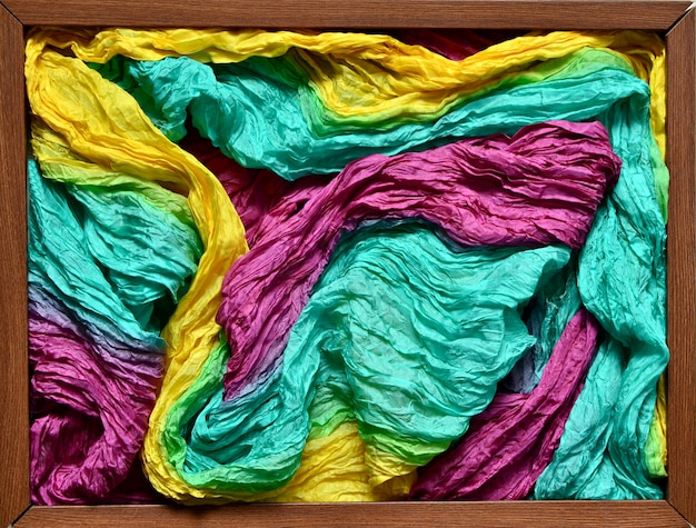 Wooden picture frame filled with fabric with silk fabric of yellow, cyan and purple colors