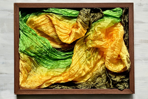 Wooden picture frame filled with fabric with silk fabric of yellow, green and brown colors