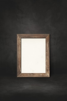 Wooden picture frame leaning on a black wall. presentation mockup template