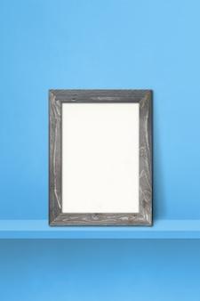 Wooden picture frame leaning on a blue shelf. 3d illustration. blank mockup template. vertical background