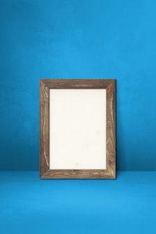 Wooden picture frame leaning on a blue wall. blank mockup template