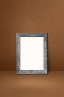Wooden picture frame leaning on a brown wall. blank mockup template