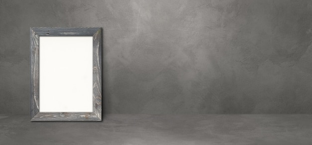 Wooden picture frame leaning on a dark concrete wall. blank mockup template. horizontal banner