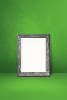 Wooden picture frame leaning on a green wall. blank mockup template