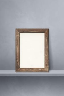 Wooden picture frame leaning on a grey shelf. 3d illustration. blank mockup template. vertical background