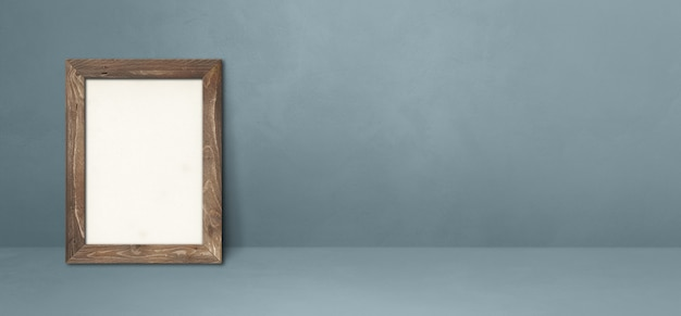 Wooden picture frame leaning on a grey wall. blank mockup template. horizontal banner